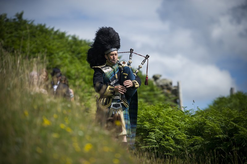 piper-playing-bag-pipes-outside-down-to-beach.jpg