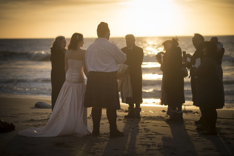 guests-group-together-on-beach-sunset-getting-married.jpg